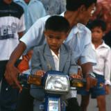 Boy with his father on a motorcycle in Saigon, Vietnam